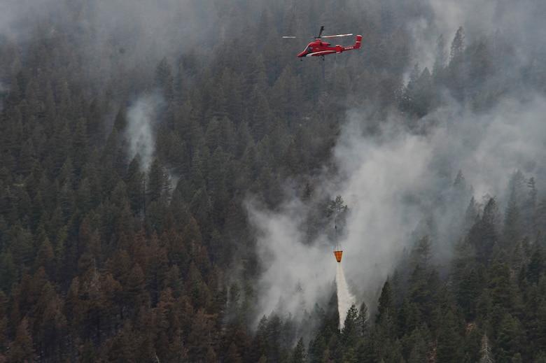 A helicopter dumps water on the Waldo Canyon Fire that has spread to the outskirts of the Air Force Academy, Colo., June 28. The Waldo Canyon fire has destroyed over 18,000 acres in the Colorado Springs area. (U.S. Air Force photo by Staff Sgt. Christopher Boitz)