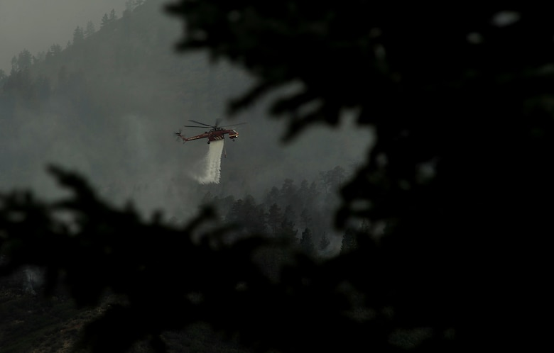 A helicopter drops water on the fire as firefighters continued to battle the blaze that burned into the evening hours in Waldo Canyon on the U.S. Air Force Academy June 27, 2012. (U.S. Air Force Photo by: Master Sgt. Jeremy Lock)