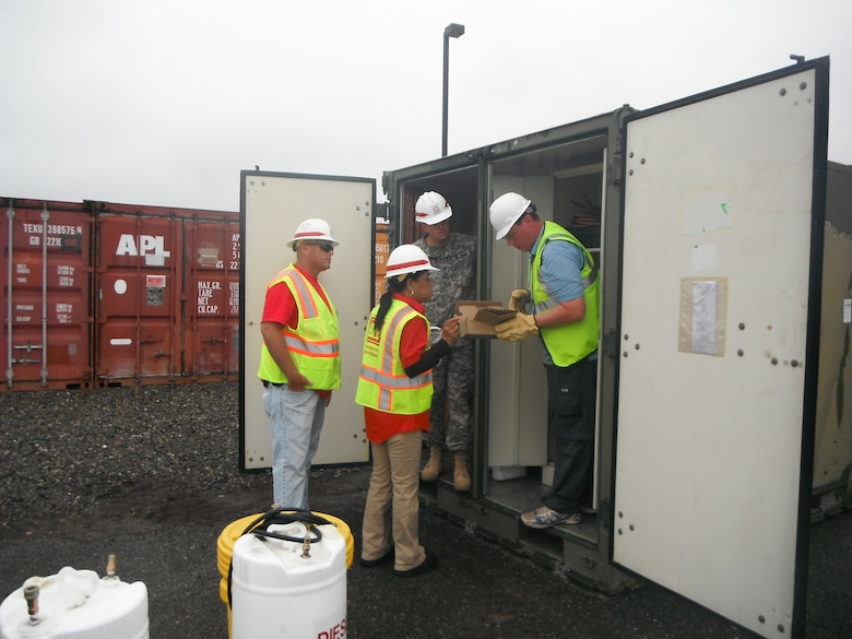 """TACOMA, Wash. — Joe Tribbey, Quality Assurance Representative (left), Marsha Phillips, Logistics Specialist (middle), and Sgt. First Class Douglas Eshenbaugh, 249th Engineer Battalion """"Yard Dog,"""" inventoryi and review generator work order requests with generator support contractor during day one of the Evergreen Earthquake Exercise generator staging area located on Joint Base Lewis-McChord."""