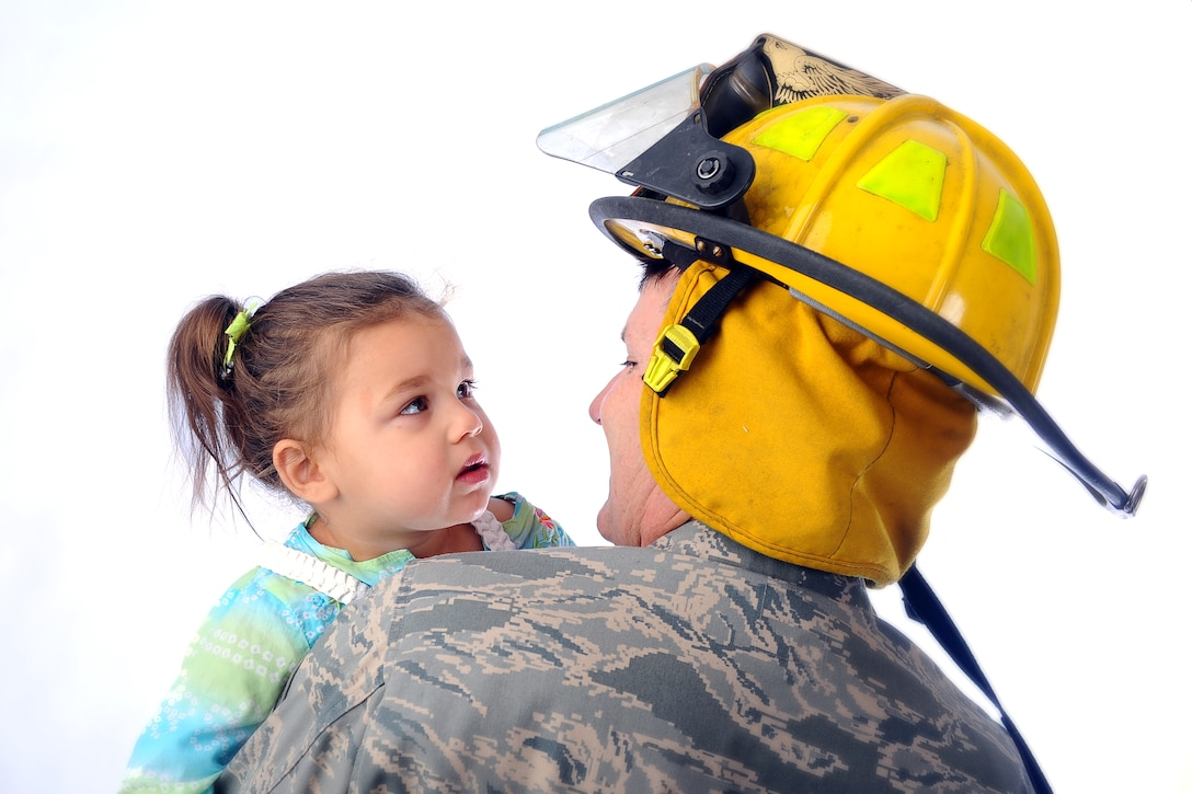 Annabella Krueger, daughter of Chad and Mirela Krueger stares into the face of U.S. Air Force Senior Master Sgt. Gary Self, a 45th Reconnaissance Squadron member and volunteer firefighter with Murray Fire and Rescue in Cass County, Neb. Annabella suffers from tuberous sclerosis complex and Self answered the call one night that saved her life. (U.S. Air Force photo by Josh Plueger/Released)