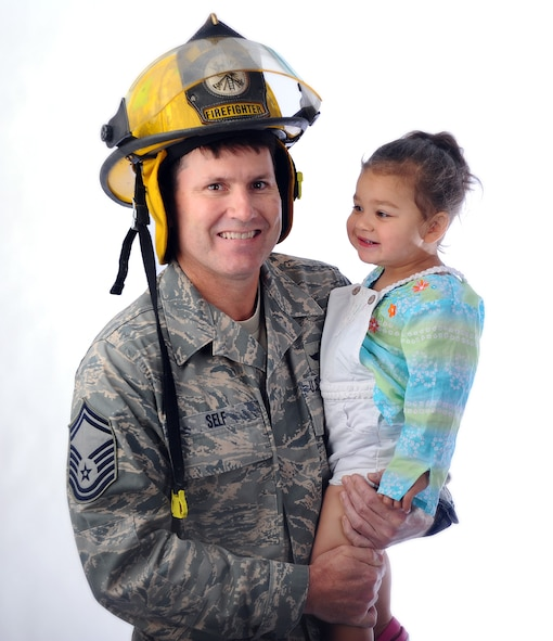 U.S. Air Force Senior Master Sgt. Gary Self, a member of the 45th Reconnaissance Squadron and Volunteer Firefighter with Murray Fire and Rescue in Cass County, Neb., holds Annabella Krueger, daughter of Chad and Mirela Krueger, whom he saved during a distress call. Annabella has a condition known as tuberous sclerosis complex, and because of tumors in her brain she has seizures, one of which almost claimed her life. (U.S. Air Force photo by Josh Plueger/Released)