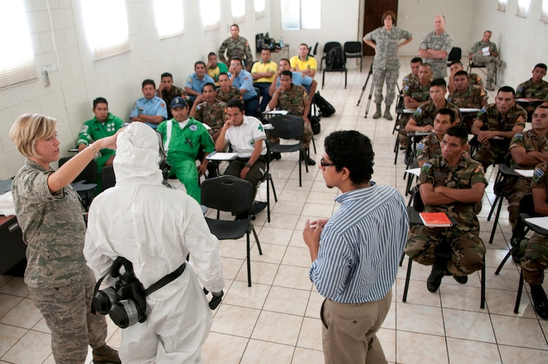 U.S. Air Force Senior Airman Alexa Shimmel (left) demonstrates on Salvadoran Soldier Carlos Alfredo Garcia Duranhow how personal protective equipment is used in an environment that may contain hazardous material as Alfredo Josue Bautista interprets June 26, 2012. Five medical personnel from the New Hampshire Air National Guard traveled here to participate in a Chemical Biological Radiological Nuclear High Yield Explosive Enhanced Response Force Package (CERFP) exchange with local authorities. (N.H. National Guard photo by Tech. Sgt. Mark Wyatt/RELEASED)