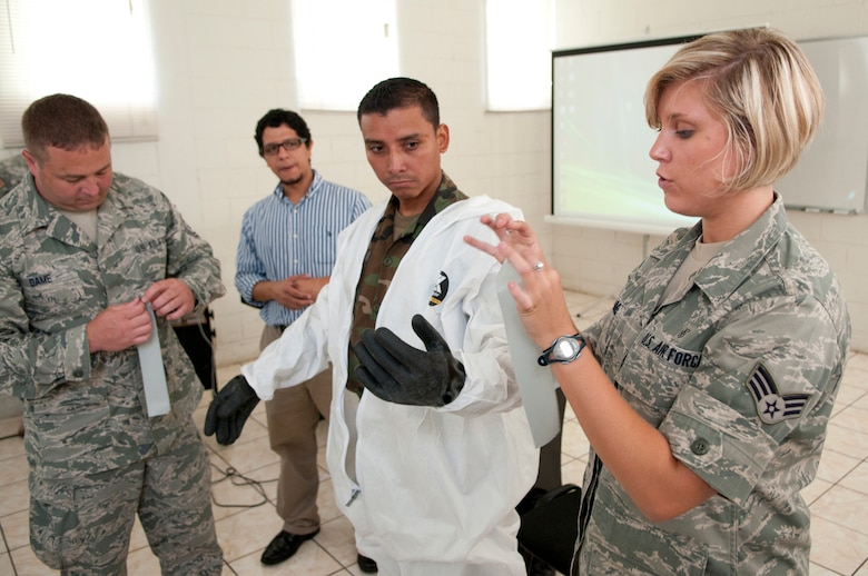 U.S. Air Force Senior Airman Alexa Shimmel (right) demonstrates on Salvadoran Soldier Carlos Alfredo Garcia Duranhow how personal protective equipment is used in an environment that may contain hazardous material as Tech. Sgt. Michael Dame assists June 26. Five medical personnel from the New Hampshire Air National Guard traveled here to participate in a Chemical Biological Radiological Nuclear High Yield Explosive Enhanced Response Force Package (CERFP) exchange with local authorities. (N.H. National Guard photo by Tech. Sgt. Mark Wyatt)