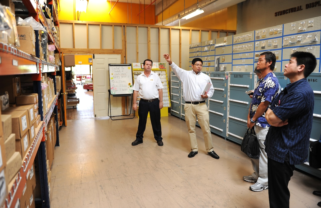 "Katsushi Miyagi, 718th Civil Engineer Squadron stock control clerk, gives a tour of the housing warehouse to the local business leaders during the ""Okinawa First"" business tour on Kadena Air Base, Japan, June 26, 2012. Local Japanese business leaders exchanged business information and discussed base acquisition procedures. The goal of Okinawan First initiative is to save the Air Force money while also supporting the local economy. (U.S. Air Force photo/Junko Kinjo)"