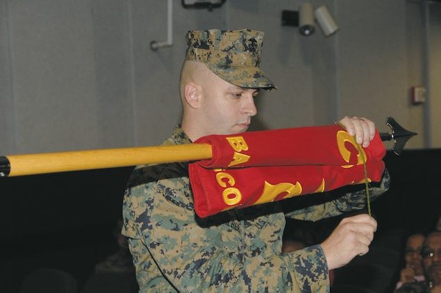 Gunnery Sgt. Gary Gilbert, band master, Albany Marine Band, furls the band's colors for deactivation at the Base Theater, Feb. 24.