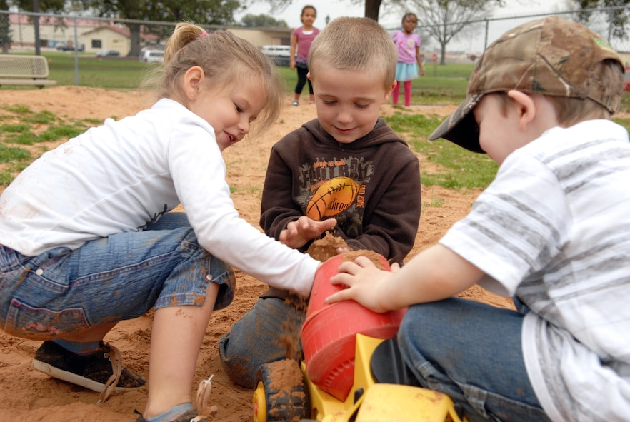 Children fill a toy truck with dirt at the Child Development Center on Barksdale Air Force Base, La., Feb. 29. Digging holes and playing in the dirt are some of the many activities the children can participate in while outside. (U.S. Air Force photo/Airman 1st Class Joseph A. Pagán Jr.)(RELEASED)