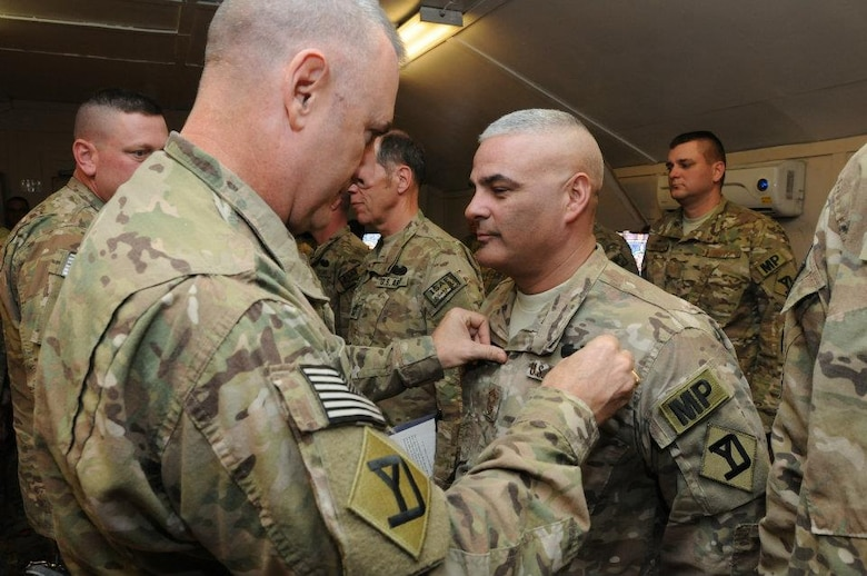 Brig. Gen. John Hammond, 26th Maneuver Enhanced Brigade commander, pins on the Combat Action Badge onto Senior Master Sgt. Emilio Rodriguez, 161st Security Forces Squadron, in Afghanistan. Sergeant Rodriguez deployed as the Provost Marshall Sergeant Major for the Kabul Capital Base Cluster from August through December 2011. Sergeant Rodriguez and his Airmen fought side-by-side next to Soldiers and coalition forces following insurgent attacks Sept. 13, 2011, on the U.S. Embassy and NATO headquarters. The Combat Action Badge was approved by the Army chief of Staff in 2005 to provide special recognition to Soldiers who personally engage or are engaged by the enemy. (Courtesy photo)