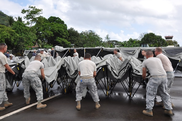 U.S. military members position themselves to set up a tent in the upright position at Tactical Operations Group 5, Legazpi City, Philippines, on March 2 for Pacific Angel-Philippines scheduled to begin March 5. The joint and combined humanitarian exercise will last six days.  (U.S. Air Force photo by Lt. Robert Howard)