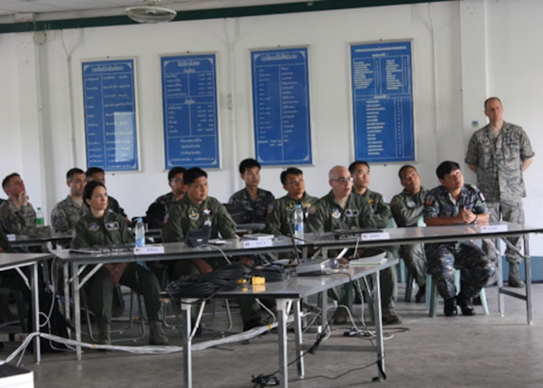 American, Thai and Singaporean Airmen listen to the Air Operations Center in-brief at the start of Cobra Gold 2012 at Camp Suranaree in Korat, Thailand. Cobra Gold is an annual Thai and U.S. co-sponsored joint and multinational exercise that is designed is to improve partner nation interoperability and capacity to conduct joint and multinational planning, operations and to respond to crises with increased speed of response, mission effectiveness, and unity of effort. (Courtesy Photo, Royal Thai Air Force)