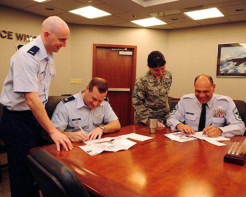 Col. Phillip Stewart, 9th Reconnaissance Wing (RW) vice commander, and Chief Master Sgt. Robert White, 9 RW command chief, fill out Air Force Assistance Fund (AFAF) pledges while 1st Lt. Jeremy Miller and Senior Master Sgt. Geri Dreibelbis, Installation Project Officers for AFAF, assist them at Beale Air Force Base, Calif. March 5, 2012.  The Air Force Assistance Fund is a program designed to raise money to assist Beale Airmen during times of need.  (U.S. Air Force photo by Staff Sergeant Jonathan Fowler/Released)
