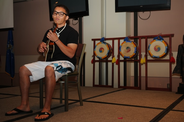 Airman 1st Class Jermiah Camacho, a 17th Comptroller Squadron financial analyst plays the ukulele during the Asian Pacific Islander Heritage Month luncheon, May 26, 2011. He learned how to play it in his native land of Guam almost six years ago. (U.S. Air Force photo/Airman 1st Class Michael Smith)