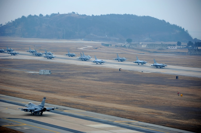 """A formation of F-16 Fighting Falcons progresses down the flight line at Kunsan Air Base, Republic of Korea, March 2, 2012, in a show of power called an """"Elephant Walk."""" The highly-maneuverable F-16s can reach a speed of 1,500 mph and are used for air-to-air combat and air-to-surface attack missions. (U.S. Air Force photo by Senior Airman Brigitte N. Brantley/Released)"""