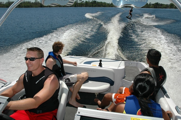 A group of friends enjoy waterskiing and boating while wearing their lifejackets.