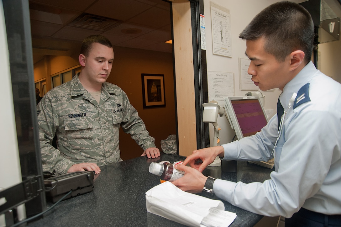 Capt. Truong-Vinh Phung, 779th Medical Support Squadron pharmacist, gives Senior Airman Harry Renninger, 11th Logistics Readiness Squadron vehicle operator, directions on medicine dosage during patient check-in at the Malcolm Grow Medical Center's Main Pharmacy on March 6. (Photo/Bobby Jones)