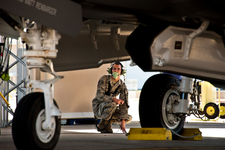 Staff Sgt. Jeremy Houser, a 33rd Aircraft Maintenance Squadron maintainer, communicates with the pilot of the F-35A Lightning II joint strike fighter during flight checks prior to the first-ever training sortie March 6 at Eglin Air Force Base, Fla.  Houser was the crew chief for the first sortie.  (U.S. Air Force photo/Samuel King Jr.)