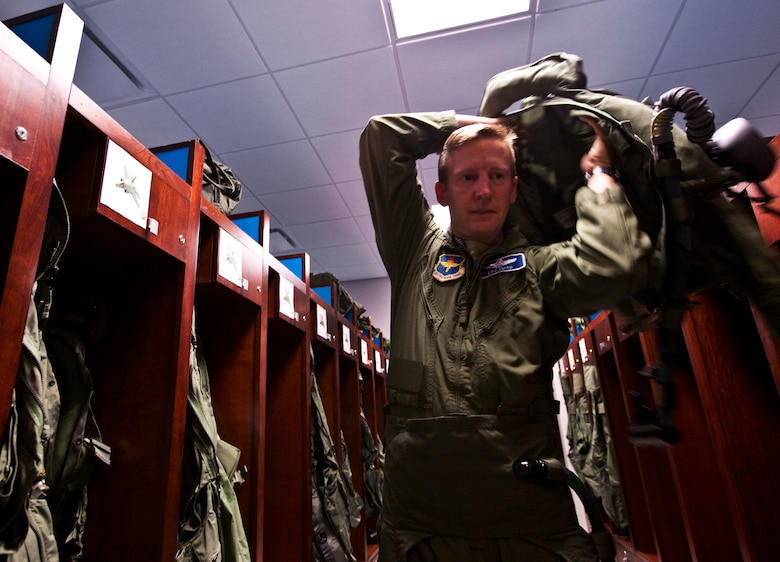 Lt. Col. Eric Smith, the 58th Fighter Squadron director of operations, puts on his flight gear prior to stepping to the F-35A Lightning II joint strike fighter for its first-ever training sortie March 6 at Eglin Air Force Base, Fla.  Smith is the first Air Force pilot qualified to fly the F-35.  (U.S. Air Force photo/Samuel King Jr.)