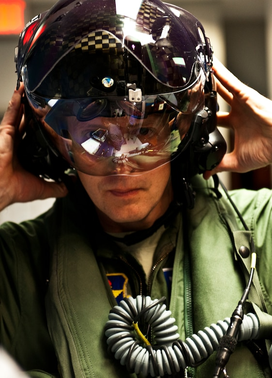 Lt. Col. Eric Smith, the 58th Fighter Squadron director of operations, secures his helmet for testing prior to stepping to the F-35A Lightning II joint strike fighter for its first-ever training sortie March 6 at Eglin Air Force Base, Fla.  Smith is the first Air Force pilot qualified to fly the F-35.  (U.S. Air Force photo/Samuel King Jr.)