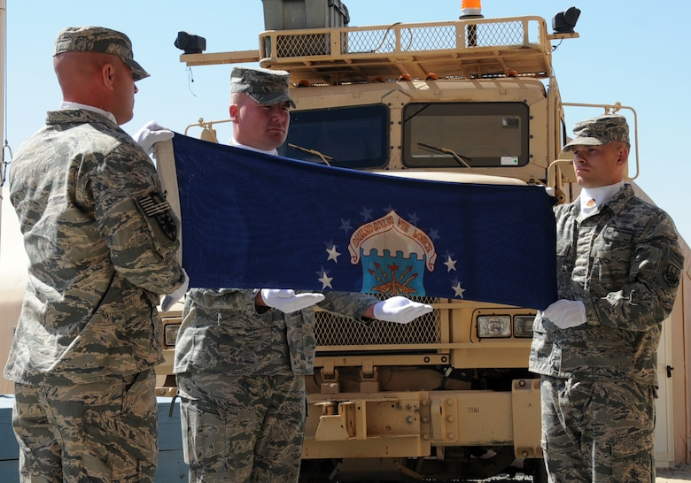 """U.S. Air Force 387th Expeditionary Logistics Readiness Squadron combat truckers fold the Air Force flag during their inactivation ceremony at an undisclosed location in Southwest Asia, March 6, 2012. The 387th ELRS participated in the largest retrograde of cargo and personnel since World War II; U.S. Central Command approved the 387th ELRS as """"mission complete"""" and authorized them to inactivate on Dec. 20, 2011. (U.S. Air Force photo by Staff Sgt. James Lieth/Released)"""