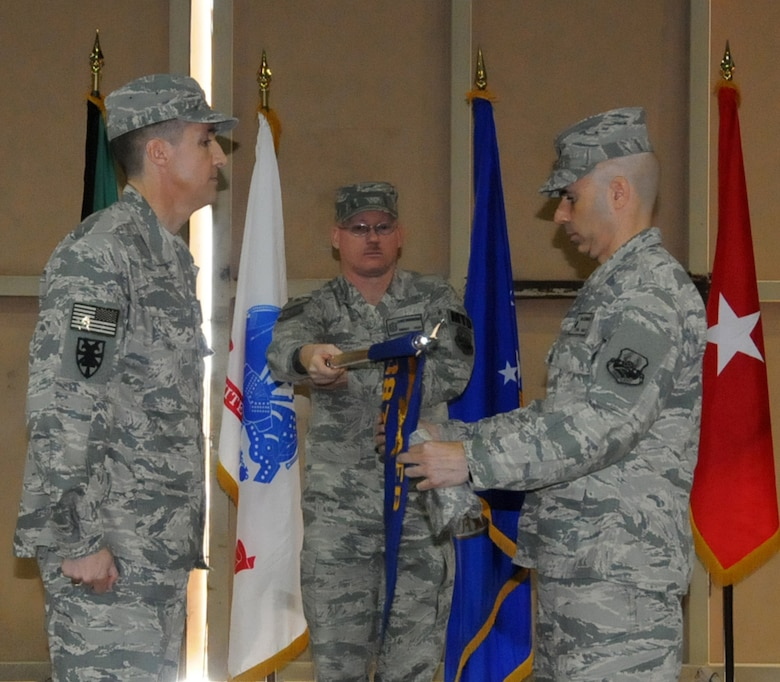 """U.S. Air Force Lt. Col. John O'Connor, commander of the 387th Expeditionary Logistics Readiness Squadron, furls his squadron's colors during an inactivation ceremony at an undisclosed location in Southwest Asia, March 6, 2012. The 387th ELRS participated in the largest retrograde of cargo and personnel since World War II; U.S. Central Command approved the 387th ELRS as """"mission complete"""" and authorized them to inactivate on Dec. 20, 2011. (U.S. Air Force photo by Staff Sgt. James Lieth/Released)"""