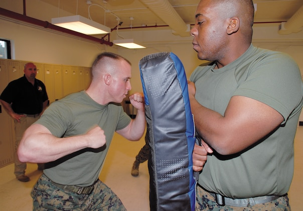 Cpl. Martin Lavigne, left, military police officer, Marine Corps Police Department, drives an elbow strike into the pad of Cpl. Sheldrick Thomas, motor transportation operator, licencing office, Garrison Mobile Equipment, Logistics Support Division, Marine Corps Logistics Base?Albany.