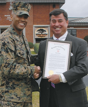 Col. Terry V. Williams, left, commanding officer, Marine Corps Logistics Base Albany, shakes hands with Jeff Sinyard, commission chairman, Dougherty County, at Schmid Field, March 1. Sinyard spoke at the base's 60th anniversary and presented a proclamation to Williams.