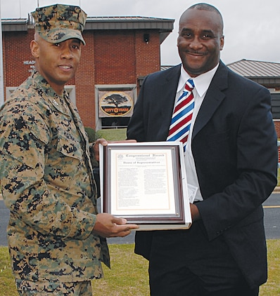 Kenneth Cutts, district director, Office of U.S. Congressman Sanford D. Bishop Jr., 2nd district, D-Georgia, presents a Congressional Record to Col. Terry V. Williams, commanding officer, Marine Corps Logistics Base Albany, during the base's 60th anniversary at Schmid Field, March 1.