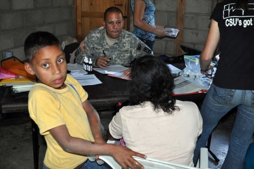 LA CEIBA, Honduras - Army Spc. Braulio Betanccourt listens to a woman in Spanish and writes down her answers in English during a medical training and readiness exercises here March 8. The Joint Task Force-Bravo medical team, along with Mission Honduras LeMars, the Honduran military, South Dakota State University nutritional team and Honduran Ministry of Health, saw more than 280 patients on day two of the four-day MEDRETE. (U.S. Air Force photo/Capt. Candice Allen)