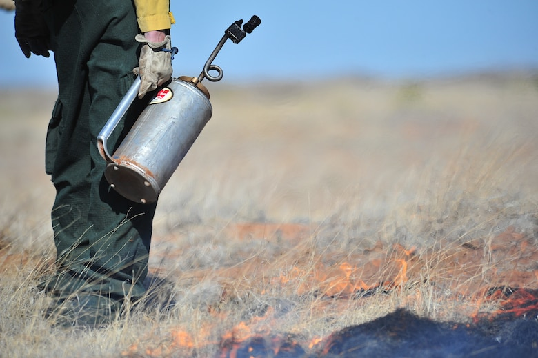 A Melrose Air Force Range firefighter uses a drip torch to start fires for a controlled burn, March 5, 2012. Controlled burns are used to deprive wild fires of fuel and to prevent them from spreading. Melrose Range provides a space for realistic training of ground and air forces and is operated by Cannon Air Force Base, N.M. (U.S. Air Force photo by Tech. Sgt. Josef Cole)