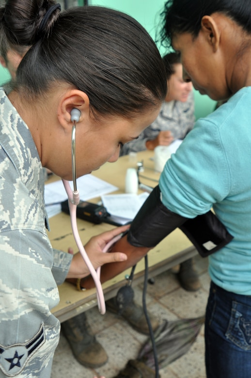SAN JUAN, Honduras - U.S. Air Force Airman 1st Class Michelle Wertz, a Medical Element medical technician, Soto Cano Air Base, Honduras, checks a woman's blood pressure during a medical readiness and training exercise here March 9. Members of the MEDRETE team saw more than 370 people from San Juan on day three of the four-day MEDRETE here.  (U.S. Air Force photo/Capt. Candice Allen)