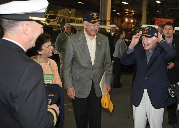 Former President Jimmy Carter tries on a new hat given to him by the crew of the USS Peleliu during a visit of the ship Mar. 10. Carter Center members flew from all parts of the U.S. for the Carter Center Winter Weekend and were able to take a tour of the ship and learn about the capabilities of the 15th Marine Expeditionary Unit.