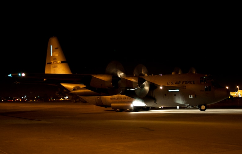 """In the early morning darkness of Mar. 11, 2012 a Minnesota Air National Guard C-130 H3 """"Hercules"""" cargo aircraft taxis towards the Minneapolis – St. Paul international runway with all four engines turning.  Over 30 Airmen of the 133rd Airlift Wing deployed to Afghanistan in support of Operation Enduring Freedom on Mar. 11, 2012. USAF official photo by Tech. Sgt. Erik Gudmundson"""