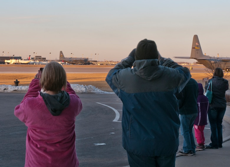 """Family members watch a C-130 H3 """"Hercules"""" take off with about 30 Minnesota Air National Guard Airmen to Afghanistan in support of Operation Enduring Freedom on March 9, 2012 at the St. Paul Air National Guard base. USAF official photo by Senior Master Sgt. Mark Moss"""