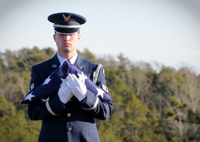 Senior Airman Zackery Benton of the 102nd Honor Guard prepares to unfold a flag in honor of a fallen veteran at the Bourne National Cemetery Jan. 19. (National Guard photo by Tech. Sgt. Kerri Cole/Released)