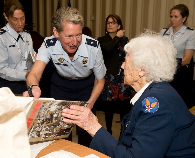 Elaine Harmon, right, one of the Women Airforce Service Pilots of World War II, autographs a book for Brig. Gen. Dana Born during the Joint Women's Leadership Symposium Mar. 6, 2012, at the National Harbor in Washington, D.C. This event offered more than 1,700 women from all Service branches the opportunity to focus on professional and leadership development. (U.S. Air Force photo by Master Sgt. Jeanette Spain)
