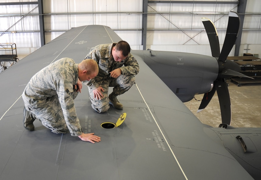 U.S. Air Force Staff Sgt. Shawn Cushman and Airman 1st Class Danny Beckwith, 522nd Special Operations Squadron crew chiefs, perform an inspection atop an MC-130J Commando II at Cannon Air Force Base, N.M., March 7, 2012. Crew chiefs must ensure aircraft configurations meet Air Force Special Operations Command standards before they are cleared for flight. (U.S. Air Force photo by Airman 1st Class Alexxis Pons Abascal)