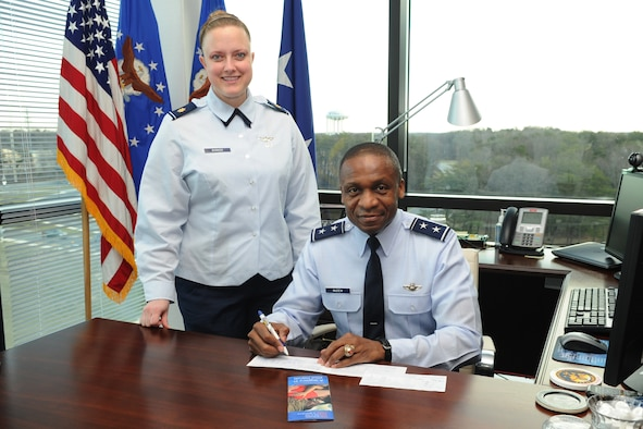 """Maj. Michelle Barker, Air Force Assistance Fund lead project officer, assists Air Force District of Washington Commander Maj. Gen. Darren W. McDew in contributing to the 2012 campaign. AFDW will have the opportunity to give from March 12 through April 20. """"What is special about this campaign, what makes it different than all the rest, is that it directly gives back to our people,"""" said Barker. (U.S. Air Force photo by Tech. Sgt. Raymond Mills)"""