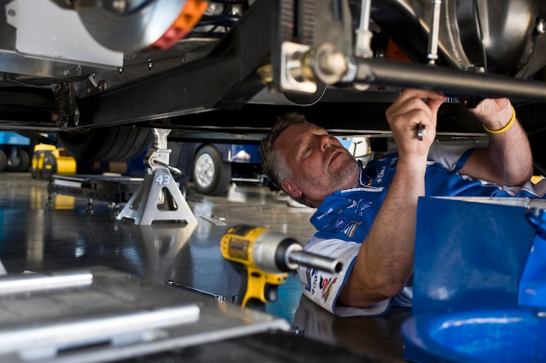 David Doyle, underneath mechanic, performs final adjustments on the Air Force-sponsored No. 43 car prior to the start of the Sprint Cup Series Race at the Las Vegas Motor Speedway qualifying round March 9, 2012, in Las Vegas. The driver, Aric Almirola, competed in the NASCAR Sprint Cup Kobalt Tools 400 Sunday at the Las Vegas Motor Speedway. (U.S. Air Force photo by Airman 1st Class Daniel Hughes)