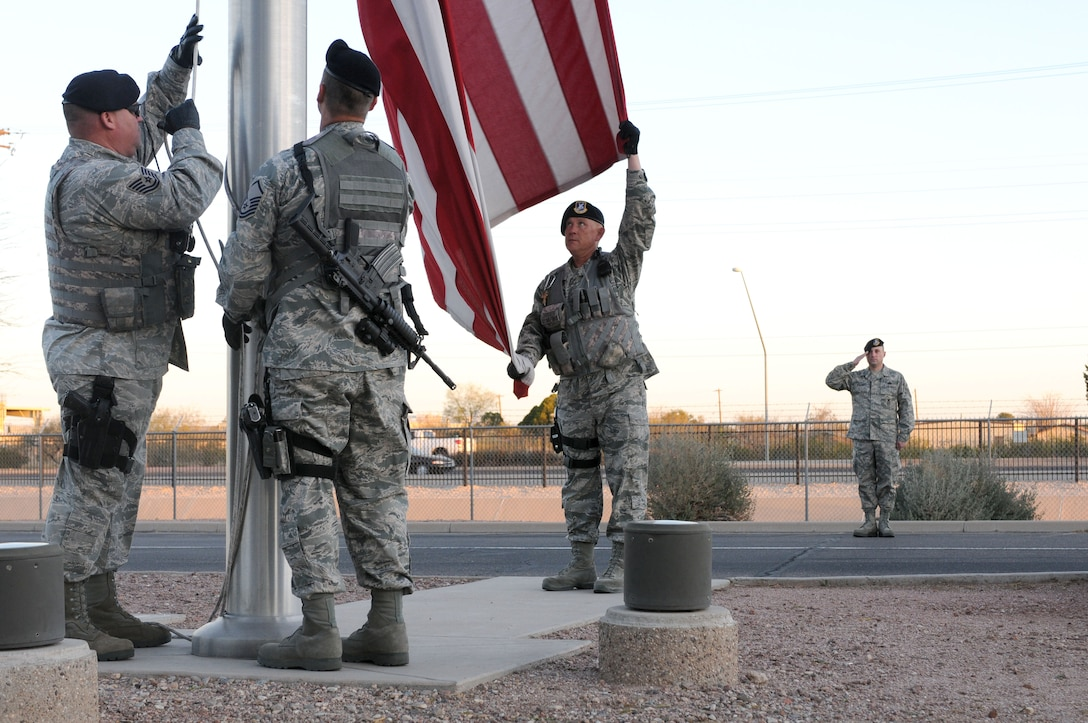 Tech. Sgt. Michael Royval, Master Sgt. Vince Muskiet and Master Sgt. Jeff Thornsberry raise the U.S. flag Feb. 27 at the 162nd Fighter Wing at Tucson International Airport while Master Sgt. James Mulcahey salutes. Even if the National Anthem isn't played, Airmen on base are reminded to stop and salute if they see this ceremony occurring on base and drivers are reminded to pull over and stop until it's completed. (U.S. Air Force photo/Maj. Gabe Johnson)