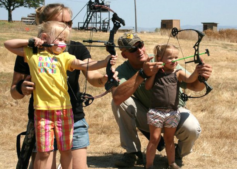 (Right) Master Sgt. Chad Hepner, 9th Medical Group first sergeant, and his wife (left) Staff Sgt. Michelle Hepner, 9th Force Support Squadron personnel, work with their daughters on archery skills at the Rod and Gun Club at Beale AFB, Calif. Master Sgt. Hepner has served as a volunteer base game warden at Beale and prior duty stations for 11 years during his career. (U.S. Air Force courtesy photo)