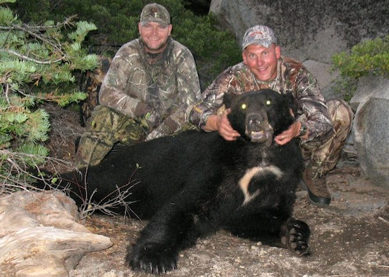 (Right) Master Sgt. Chad Hepner, 9th Medical Group first sergeant, and (left) Master Sgt. Nathan Schmidt, 9th Security Forces Squadron first sergeant, pose with a black bear Hepner harvested in California during the 2011 bear season. Hepner hunts so much that his family hasn't bought a cut of meat from a grocery store in 19 years. (U.S. Air Force courtesy photo)