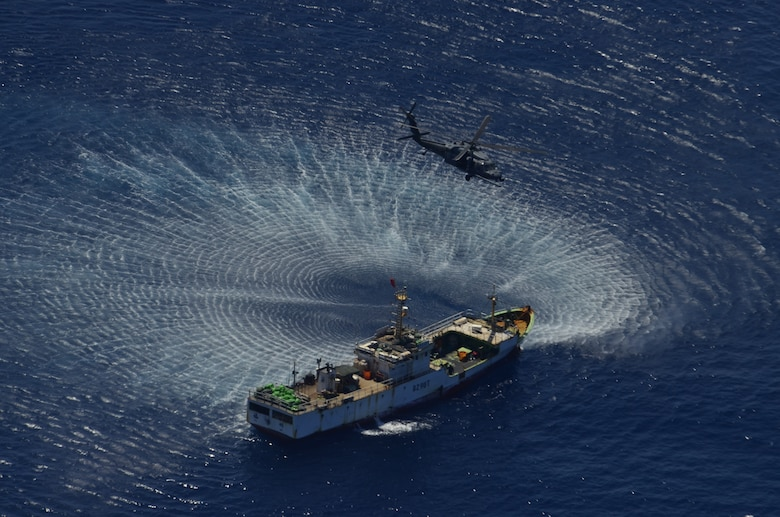 An HH-60G Pave Hawk rescue helicopter from the 129th Rescue Wing hovers over the Chinese fishing vessel Fu Yuan Yu #871, March 12, 2012. Guardian Angel Pararescuemen from the wing rescued two fishermen who were burned in a diesel fire onboard the vessel more than 700 miles off the coast of Acapulco, Mexico. (Air National Guard photo by Airman 1st Class John Pharr)