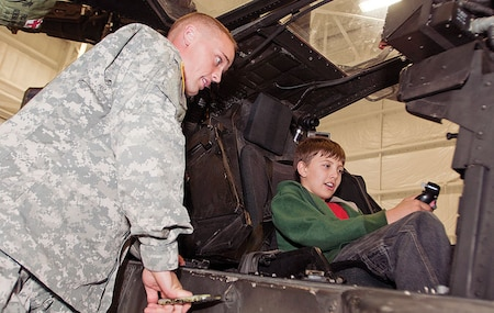 A Fort Riley AH-64 Apache Longbow helicopter pilot gives a fifth-grader from Wamego's West Elementary School a tour of his aircraft May 20 during a field trip to post. Soldiers with the 1st ARB, 1st Avn. Regt., CAB, are partnered with the school as part of Fort Riley's Adopt-a-School program.