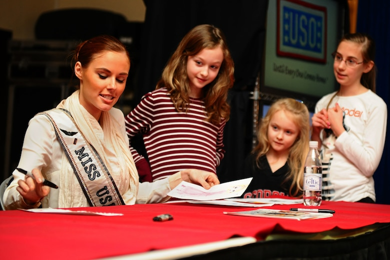 SPANGDAHLEM AIR BASE, Germany – Alyssa Campanella, Miss USA 2011, autographs pictures for, from right, Maren Thiel, daughter of Tina Thiel; and Megan Rice and Hannah Rice, daughters of Andrew Rice, 52nd Force Support Squadron, during a USO and Armed Forces Entertainment tour at the Brick House here March 13. The purpose of the tour was to boost morale and show support to U.S. service members and their families stationed in Germany. (U.S. Air Force photo by Airman 1st Class Matthew B. Fredericks/Released)