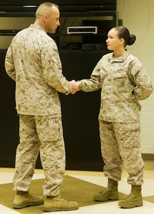 Sgt. Maj. Robert G. VanOostrom presents Cpl. Nicole Dickinson, ammunition technician, Logistics Support Division, MCLB Albany, with a command coin for winning the meritorious corporal board, in front of her peers.
