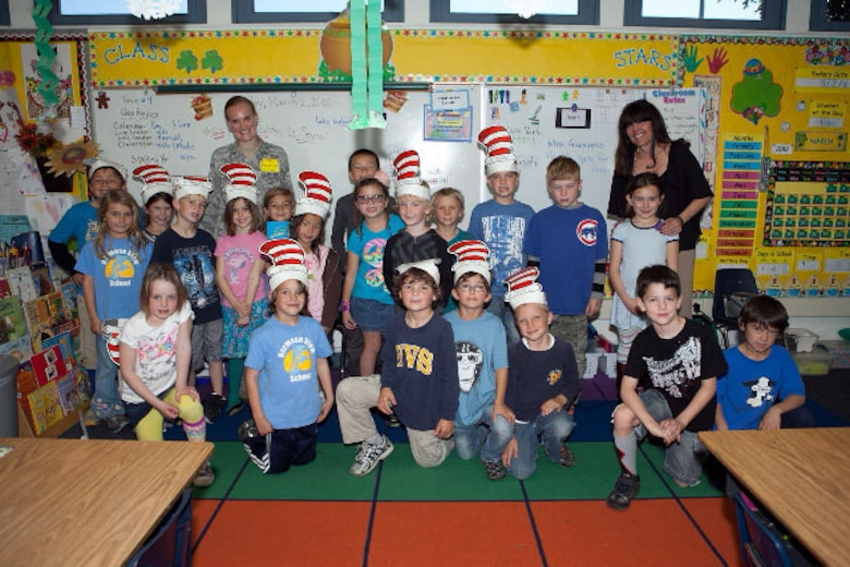 1st Lt. Kristin Hoover poses for a group picture with Mrs. Ramirez's first grade class during Read Across America at Hermosa View Elementary School, Hermosa Beach, Calif. Photo courtesy of Military Satellite Communications Systems Directorate.
