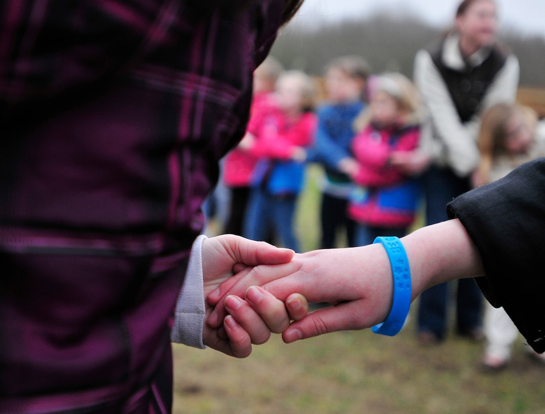 ROYAL AIR FORCE LAKENHEATH, England - Girls perform a friendship circle during the Girl Scouts' 100th Birthday event at Defender's Park March 12, 2012. The event, planned by the members of Anglia Brownie Troop 43, included a group sing-along, friendship circle, cupcakes and fun. (U.S. Air Force photo by Senior Airman Tiffany M. Deuel)