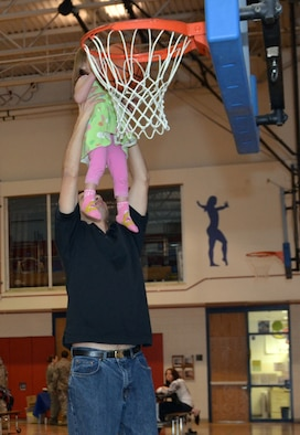 Capt. Ray Magallanez lifts his daughter, 2-year-old Anleigh, to the basket in the Air Force Academy's Youth Center March 8, 2012, during a deployment networking summit. The event was organized by the Academy's Airmen and Family Readiness Center to build relationships among families of service members who have recently deployed, have deployed or are about to deploy. Magallanez is an instructor in the Academy's Mathematical Sciences Department. (U.S. Air Force photo/Amber Baillie)