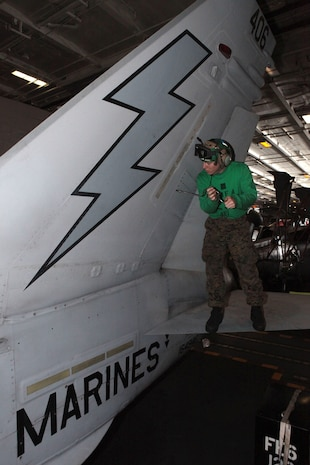 Lance Cpl. Spencer Holm, Marine Fighter Attack Squadron 251 avionics technician, removes a panel while aboard aircraft carrier USS Enterprise, March 19. The technicians are some¬times required to remove panels and other various aircraft components to access electronic systems.