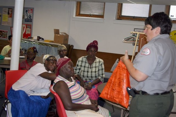 ILLINOIS — Lou Ann McCracken, a natural resources specialist with the U.S. Army Corps of Engineers Mississippi River Project, presents water safety information to local refugees, educating them on hidden dangers in the river.