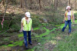Project Manager Linda Adcock (left) and Geologist Sarah Mackey, U.S. Army Corps of Engineers Nashville District, mark a location where environmentally-safe green-yellow dye has exited from a rock formation indicating where seepage is making its way from the drill site.